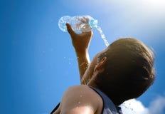 飞溅和倾吐从瓶的年轻人淡水在他的面孔 免版税图库摄影
