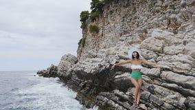 飞溅在一个亭亭玉立的女孩的立场与绿色泳装的白色的层状岩石峭壁的美丽的波浪 股票视频