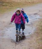 飞溅在一个泥泞的水坑的男孩和女孩 免版税图库摄影
