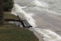 飞溅在一条坐的长凳的水接近的看法在湖sho附近 库存图片