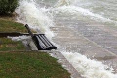 飞溅在一条坐的长凳的水接近的看法在湖sho附近 免版税库存图片