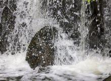飞溅在大石头的水 免版税库存照片