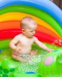 飞溅在小家伙水池的可爱的男婴 库存图片