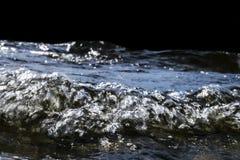 飞溅在岩石的大有风波浪 在黑背景隔绝的湖挥动飞溅 打破在一个石海滩的波浪 图库摄影