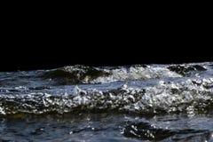 飞溅在岩石的大有风波浪 在黑背景隔绝的湖挥动飞溅 打破在一个石海滩的波浪 库存图片