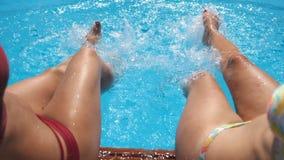 飞溅在旅馆水池的女性腿透明的水  两个朋友坐他们边缘的水池和享用 影视素材