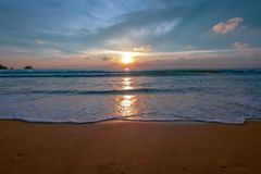 飞溅在棕色沙子海滩的海水在日落期间在普吉岛泰国 库存照片
