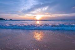飞溅在棕色沙子海滩的海水在日落期间在普吉岛泰国 库存图片