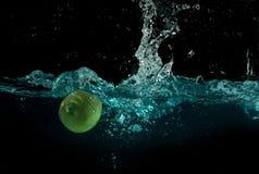飞溅在水之下的石灰 免版税图库摄影