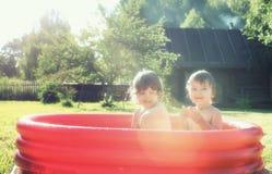 飞溅在水池的婴孩户外 免版税库存照片