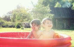 飞溅在水池的婴孩户外 免版税图库摄影