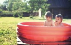 飞溅在水池的婴孩户外 免版税库存图片