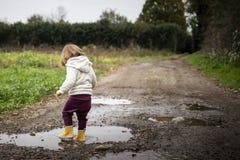 飞溅在泥泞的乡下公路的水坑的小孩 库存图片