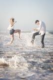 飞溅在海浪的年轻美好的夫妇在海滩 免版税库存图片