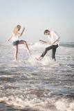 飞溅在海浪的年轻美好的夫妇在海滩 免版税图库摄影