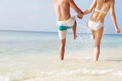 飞溅在海的夫妇细节在海滩假日 库存图片