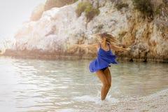 飞溅在海的美丽的少妇在海滩 库存照片