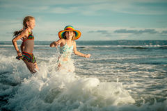 飞溅在海滩的两个姐妹 免版税库存图片