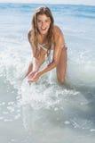 飞溅在海滩的白色比基尼泳装的美丽的微笑的妇女 库存图片
