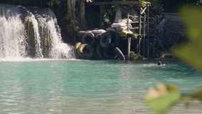 飞溅在淡水的热带瀑布和年轻女人游泳的小瀑布瀑布 美丽的热带瀑布 股票录像