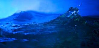 飞溅在深刻的蓝色backgroundwater的水在深刻的蓝色背景中 免版税库存图片