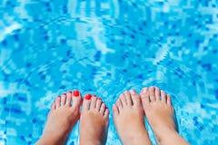 飞溅在游泳池的妇女英尺 免版税库存照片
