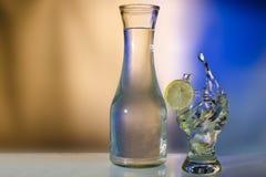 飞溅在玻璃的水与柠檬和瓶 免版税库存图片
