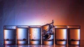 飞溅在玻璃的流体 玻璃那行在青红色背景的 免版税图库摄影