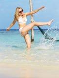 飞溅在美丽的热带海的比基尼泳装的妇女 免版税库存照片