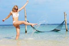 飞溅在美丽的热带海的比基尼泳装的妇女 免版税图库摄影