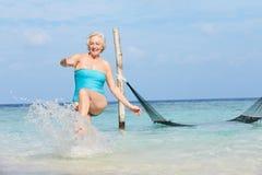 飞溅在美丽的热带海的资深妇女 库存照片