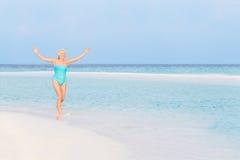 飞溅在美丽的热带海的资深妇女 免版税库存照片