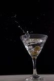 飞溅在马蒂尼鸡尾酒玻璃的伏特加酒与橄榄 免版税图库摄影