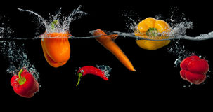 飞溅在水中的新鲜蔬菜在黑色 免版税图库摄影