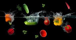 飞溅在水中的新鲜蔬菜在黑色 库存照片