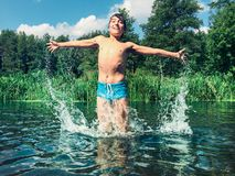 飞溅在水中的年轻男孩在夏天 免版税库存照片