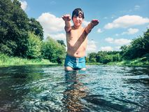 飞溅在水中的年轻男孩在夏天 库存图片
