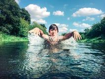 飞溅在水中的年轻男孩 库存图片