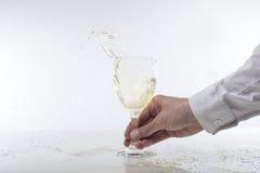飞溅在玻璃的人白葡萄酒 免版税库存照片