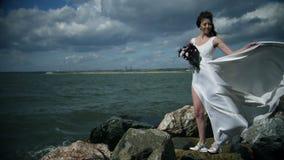 飞溅水包围一可爱的年轻女人 白色礼服的新娘在有花的海洋在她的手上站立 股票录像