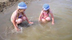 飞溅水的两个女孩在海滩 孪生倾倒在孩子之上一种热的夏日、笑声和好心情的水  影视素材