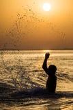 飞溅水的人在夏天日落假日期间 年轻可爱的人获得在一个热带海滩的乐趣在日落 免版税库存图片