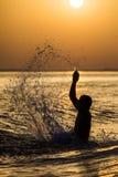 飞溅水的人在夏天日落假日期间 年轻可爱的人获得在一个热带海滩的乐趣在日落 免版税库存照片