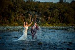 飞溅水的愉快的时兴的新婚佳偶的情感画象,当站立在河在日落期间时 库存图片