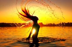 飞溅水的秀丽式样女孩与她的头发 在日落天空的女孩剪影 游泳和飞溅在夏天海滩 免版税图库摄影
