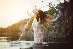飞溅水的秀丽式样女孩与她的头发 青少年的女孩游泳和飞溅在夏天海滩 库存图片