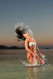 飞溅海水的女孩与她的头发 免版税图库摄影