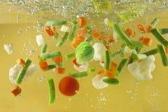 飞溅烹调概念的蔬菜在水汤 图库摄影
