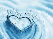 从水飞溅的心脏与在大海背景的泡影 免版税库存图片