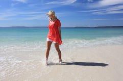 飞溅脚的愉快的妇女在海滩 免版税库存照片